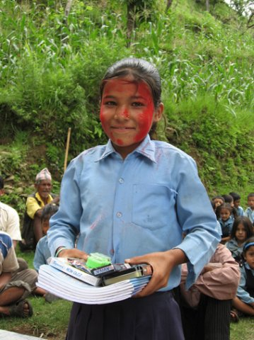 A student receiving free stationery during an event organized Sambhav Nepal