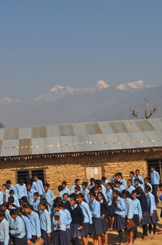 Students lined up at the morning assembly. Ganesh Mountain range in the background