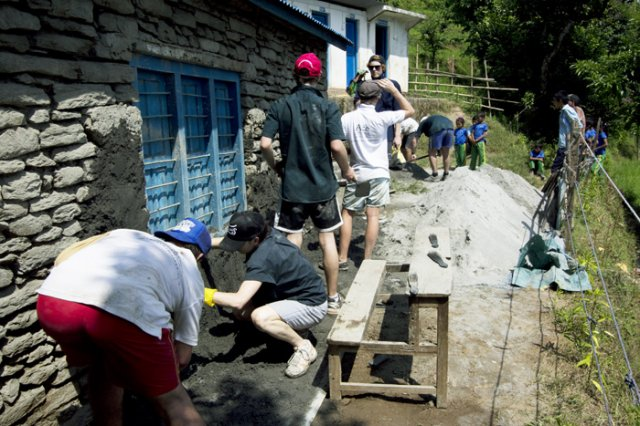 Volunteer Plastering the Rugged walls of the School